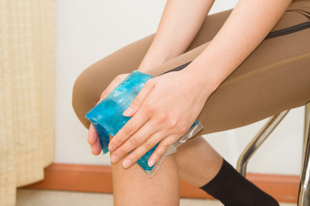woman-applying-cold-pack-swollen-hurting-knee-after-sport-injury-chrysa-vafeiadi-physio