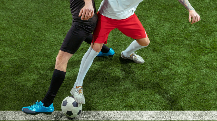 football-player-tackling-ball-green-grass-chrysa-vafeiadi-physio